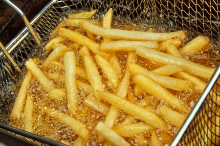 24601321 - french fries in a deep fryer closeup